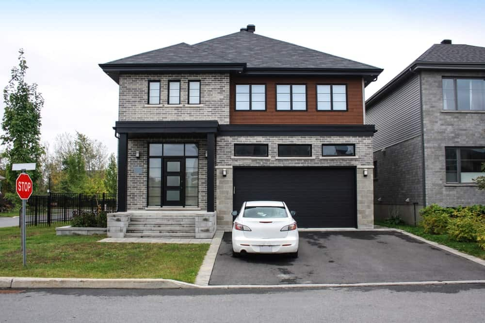 Residential zen house with one-door garage, front lawn, and asphalt driveway.