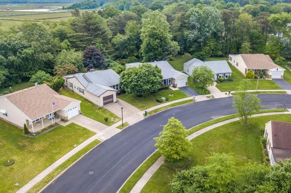 Aerial view of a row of countryside mansions with asphalt driveways for each.