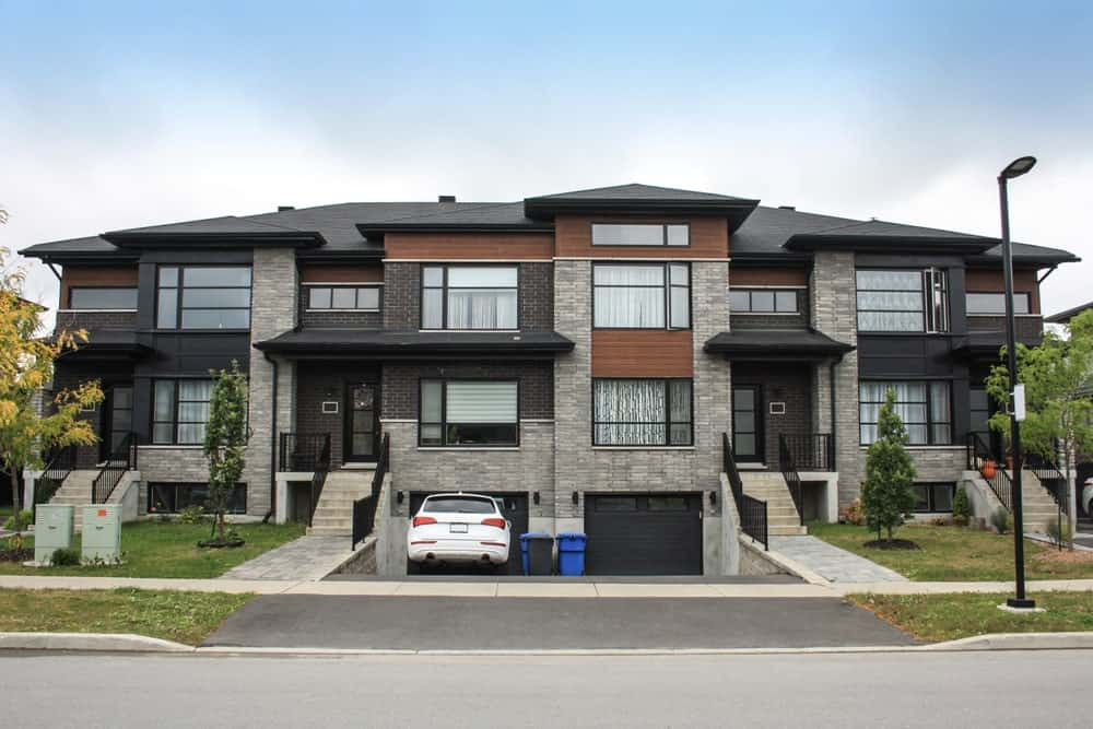 Residential mansion with sloping and asphalt driveway and multilevel interior.