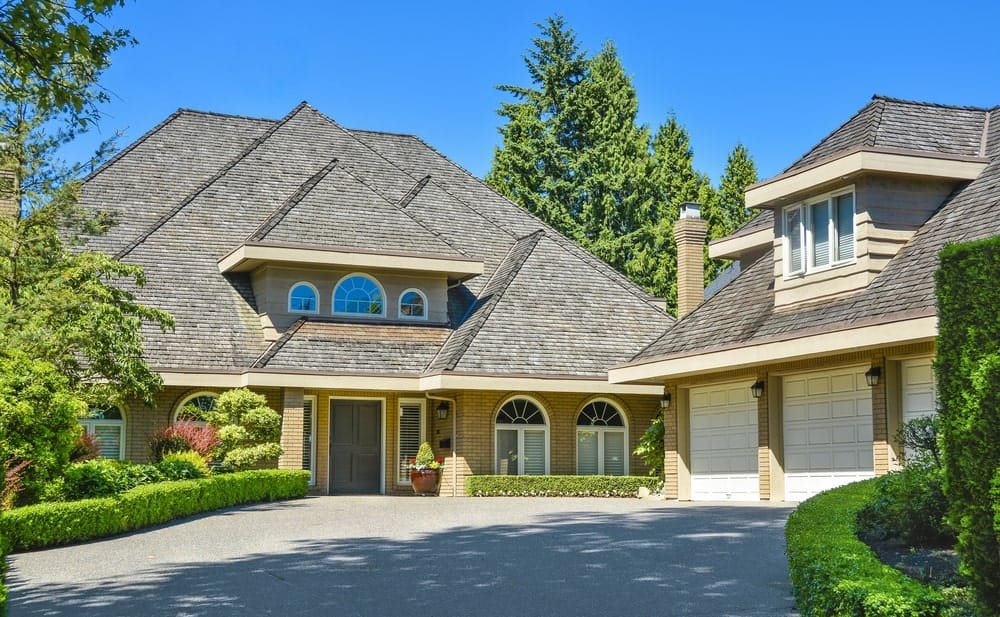 Residential mansion with triangular sloping roofing and asphalt driveway.