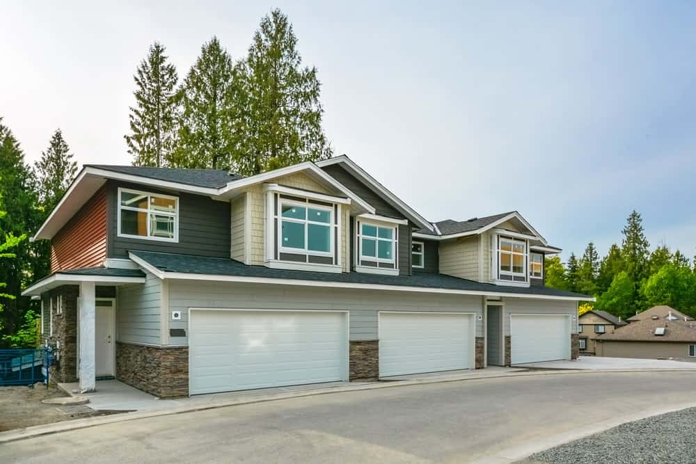 Residential triplex with three-door garage and asphalt driveway.