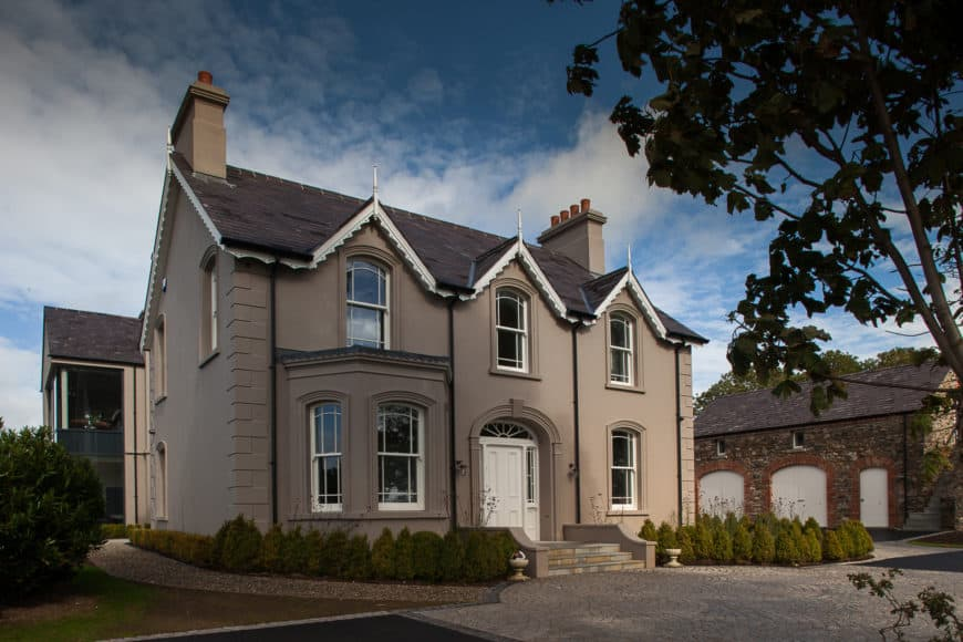 Restored country house with a gray exterior and a nice frontyard. It also has lovely walkways.