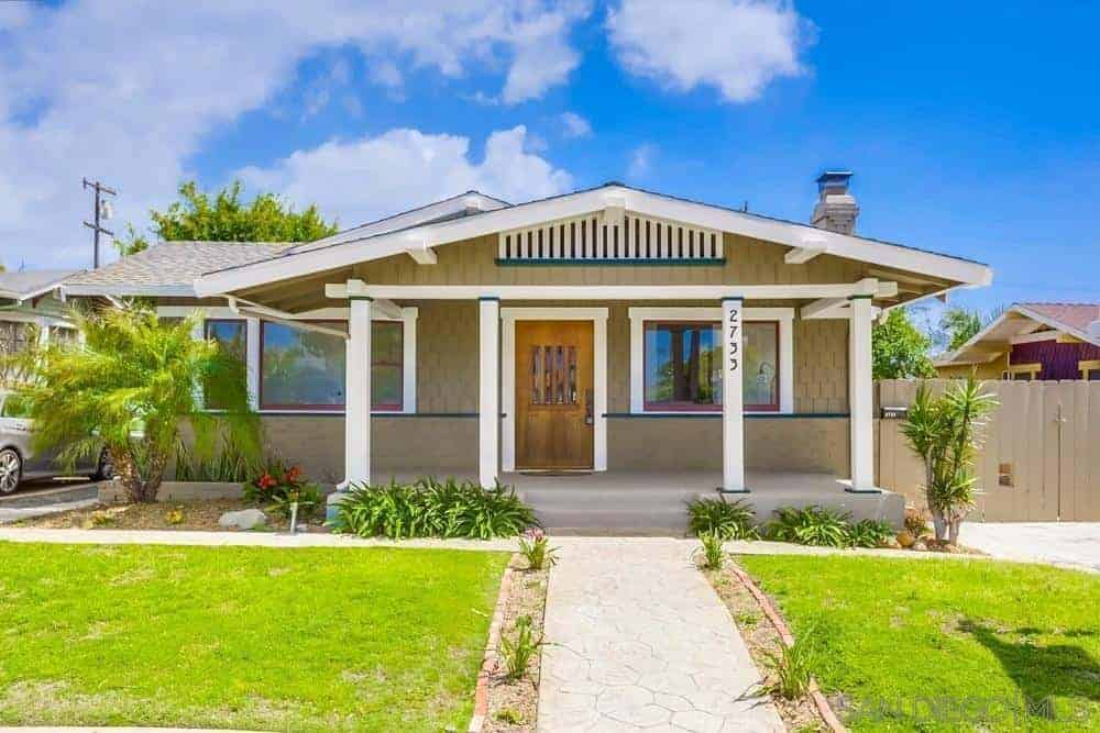 A craftsman home with a beautiful lawn and garden area along with a garage for one car.