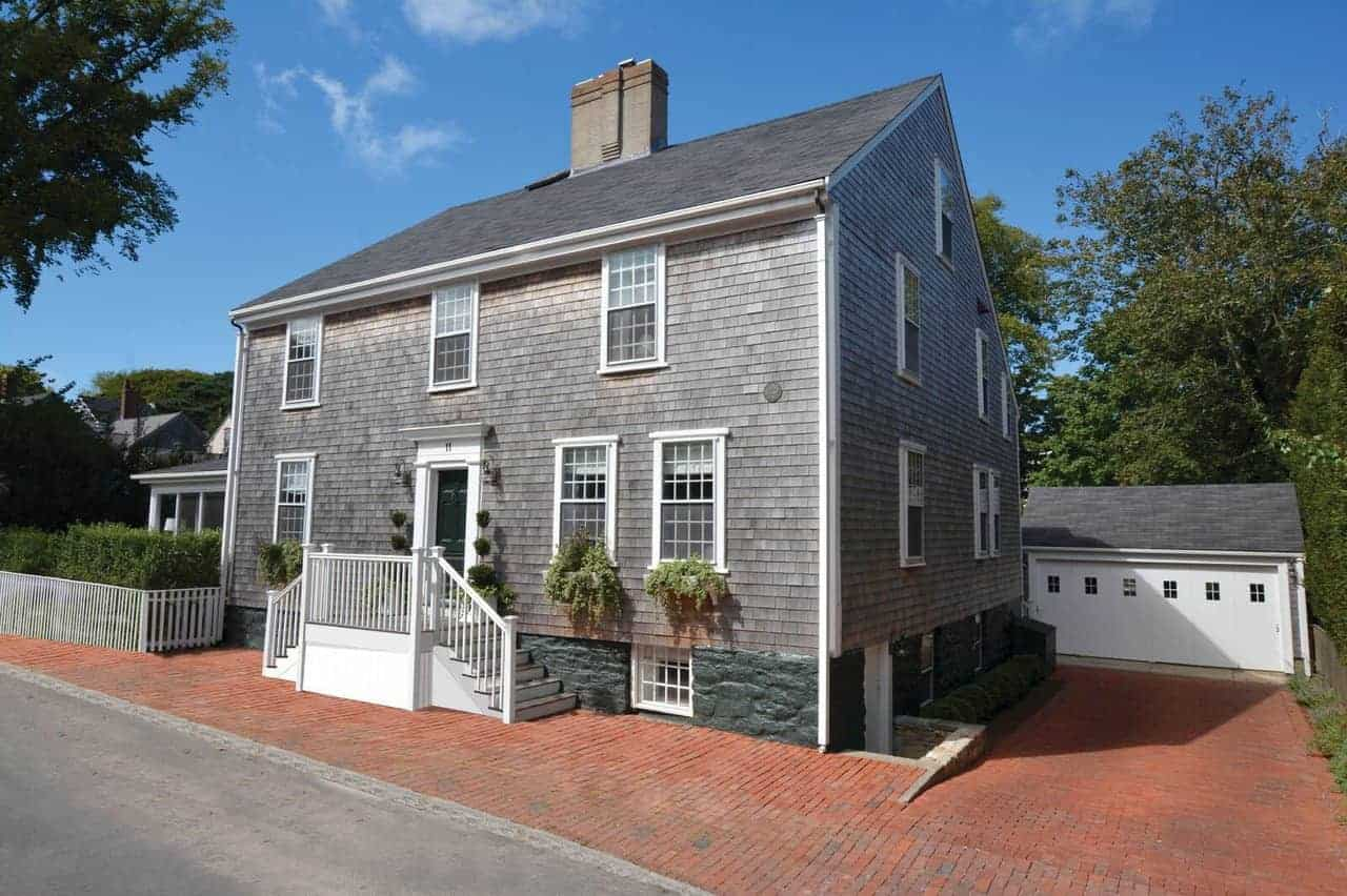 A colonial hose featuring a brick driveway leading to the home's garage. The house's exterior is painted in gray.