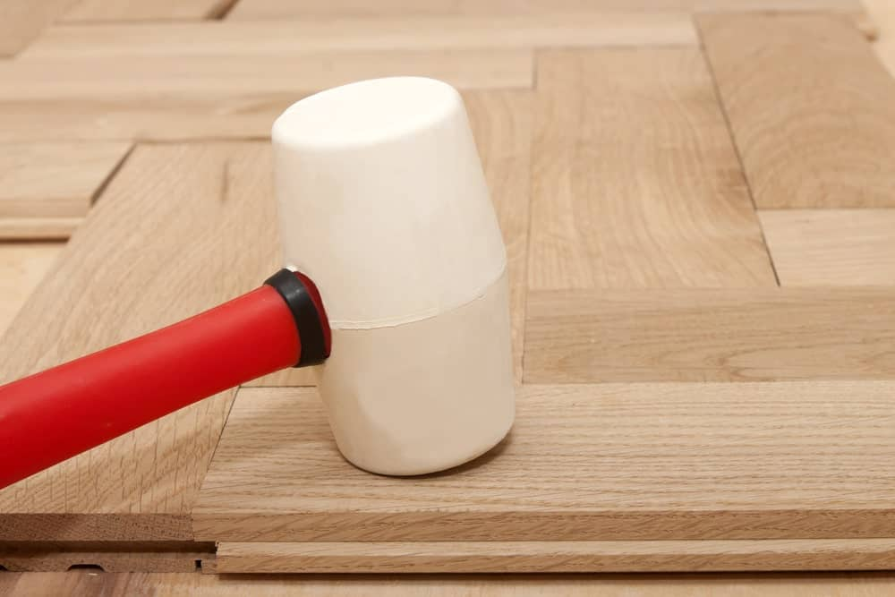 Rubber mallet on top of a wooden surface.
