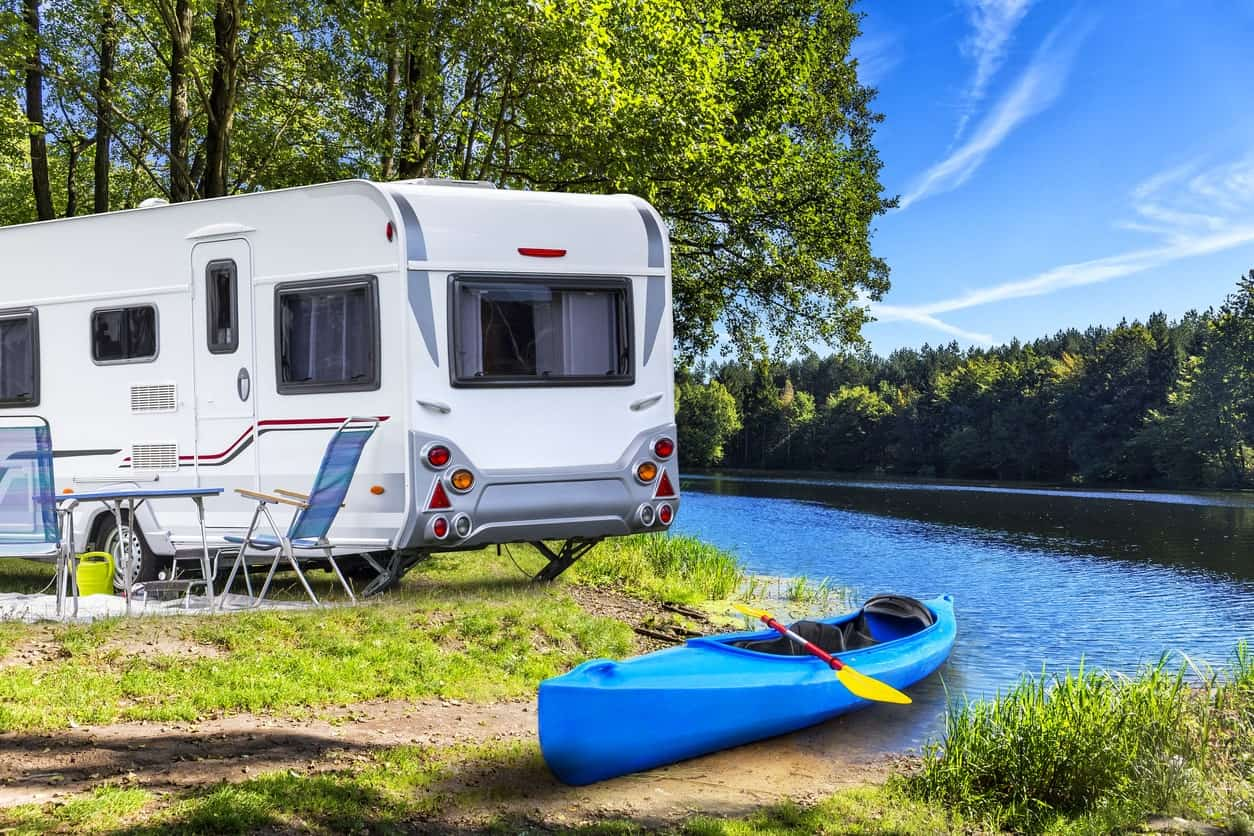 An RV trailer is parked beside a table and chairs while a canoe is docked at the edge of the lake.