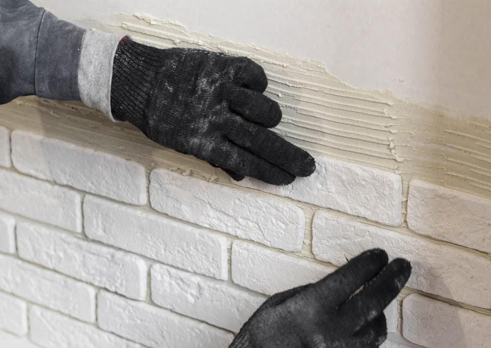 A pair of hands wearing black safety gloves touching a decorative wall.