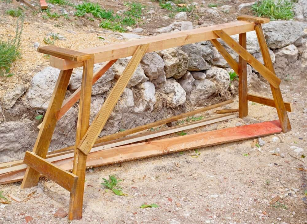 Sawhorse placed outdoors with slabs of wood at the ground soil with rocks as edging on the side.