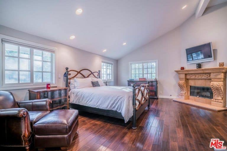 The bedroom features a hardwood floors, fireplace and a TV along with a large bed and comfortable reclining seat.