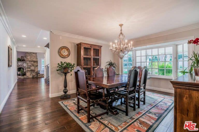 Fresh dining area offers a classy dining set that sits on a bordered rug illuminated by a candle chandelier along with natural light that flows through the white framed windows.