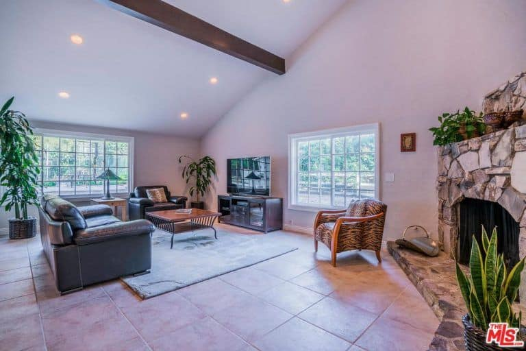 Spacious living room boasts vaulted ceiling fitted with recessed lighting along with concrete tiled flooring topped by a gray rug. It has a stone fireplace and television that sits on the wooden stand.