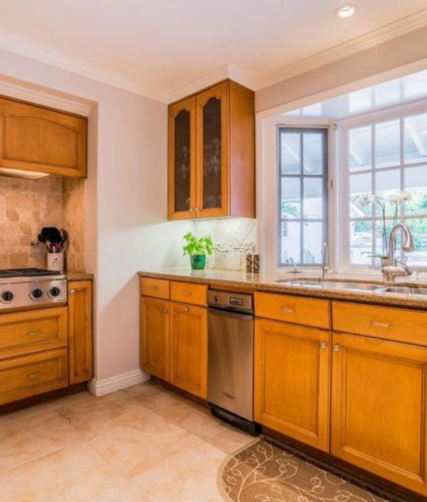 The kitchen features walnut wood cabinetry and white walls lighted by recessed ceiling lights.