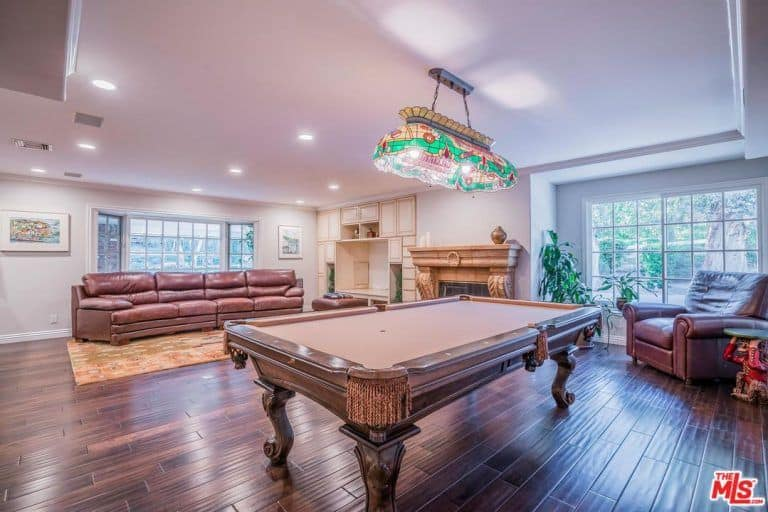 This living room boasts a leather sofa set and a fireplace along with a billiards pool set on the hardwood flooring and is lighted by a charming pendant lighting.