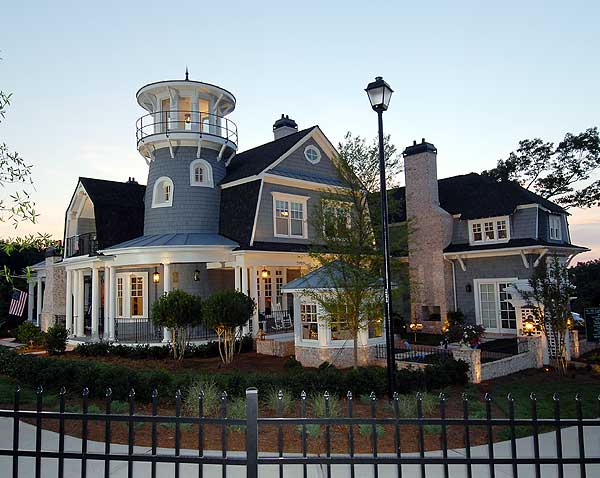 A gorgeous-looking beach house with a gray exterior. It has an iron fence and a garden area as well.