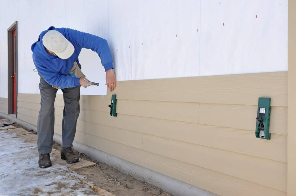Man using a siding gauge on side panels.