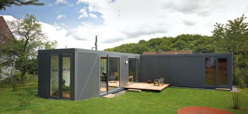 Single-story L-shaped container home with a gray exterior.