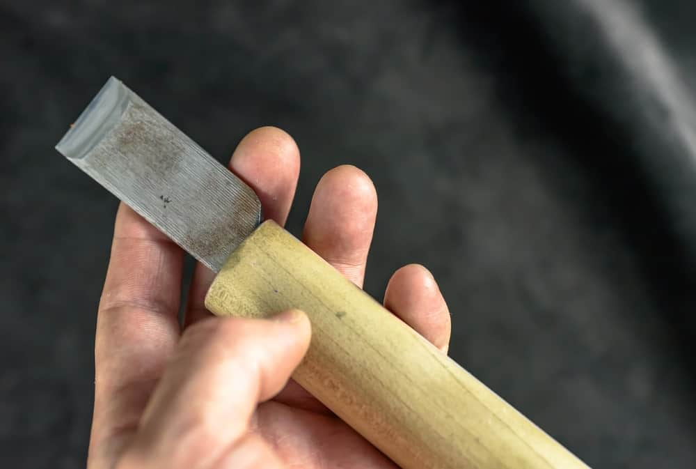 Hand showing a skiving knife.