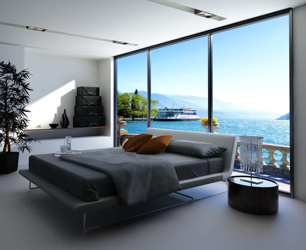 Black and white modern primary bedroom with platform bed in an apartment with floor to ceiling window.