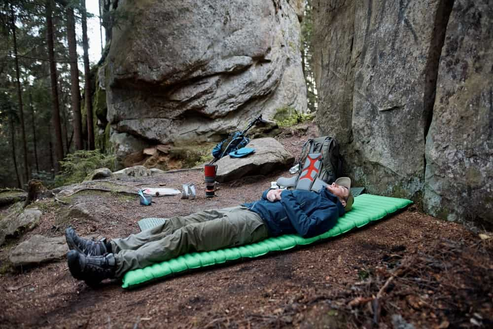 Man sleeping outdoors on a sleeping pad.