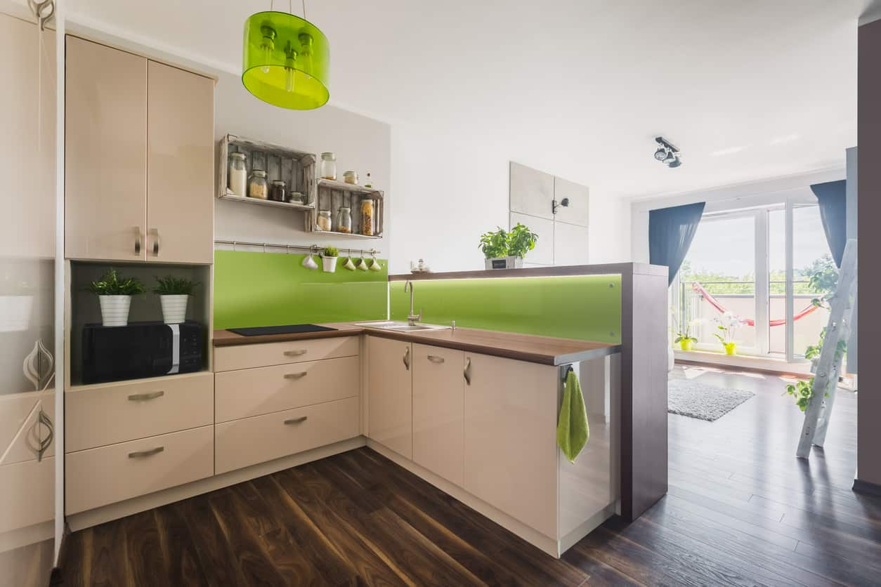 Modern small kitchen with dark wood flooring and green backsplash set against white cabinets and white ceiling.