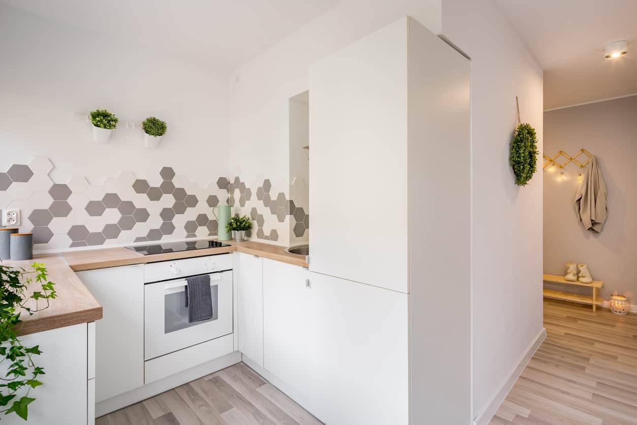 Tiny white minimalist kitchen with wood countertops. White and gray hexagon tile backsplash adds an interesting texture to the space.