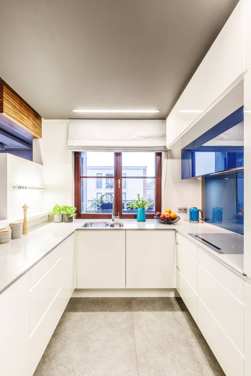 Modern blue and white u-shaped small kitchen with window above the sink.