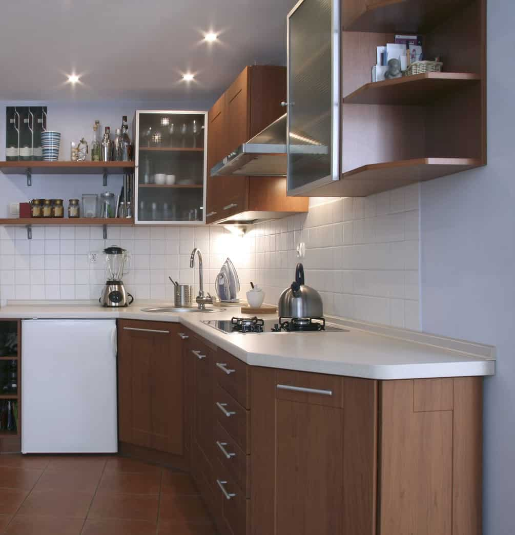 Small l-shaped kitchen with contemporary wood cabinets, open upper shelving and white backsplash. Includes half-fridge and miniature range.