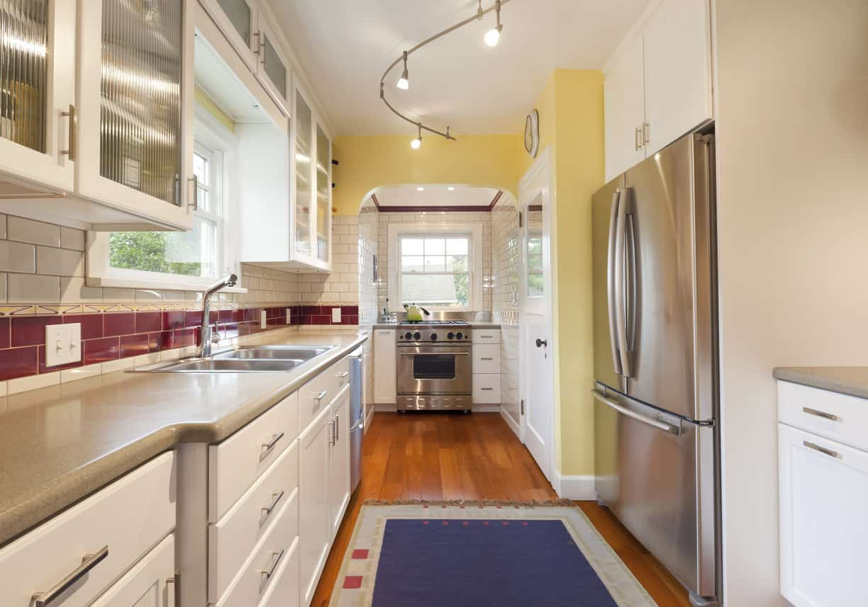 Long and narrow la-shaped kitchen newly renovated with white cabinets, yellow accent wall, stainless steel appliances and wood flooring. Again, I'm not a fan of the beige countertops, but I love the ruby red backsplash.
