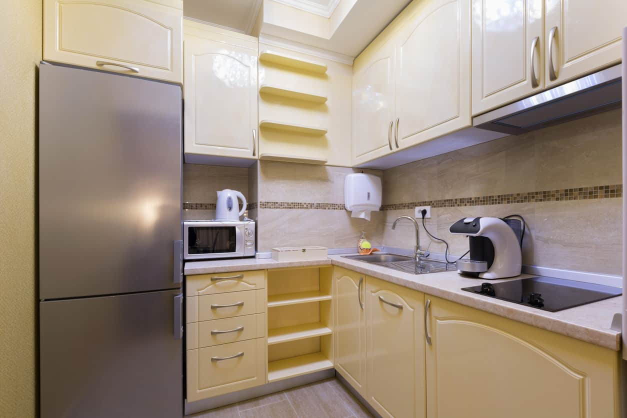 Small yellow kitchen with loads of cabinet space. Extra light emitted from skylight. I don't care for the beige backsplash - should be white.