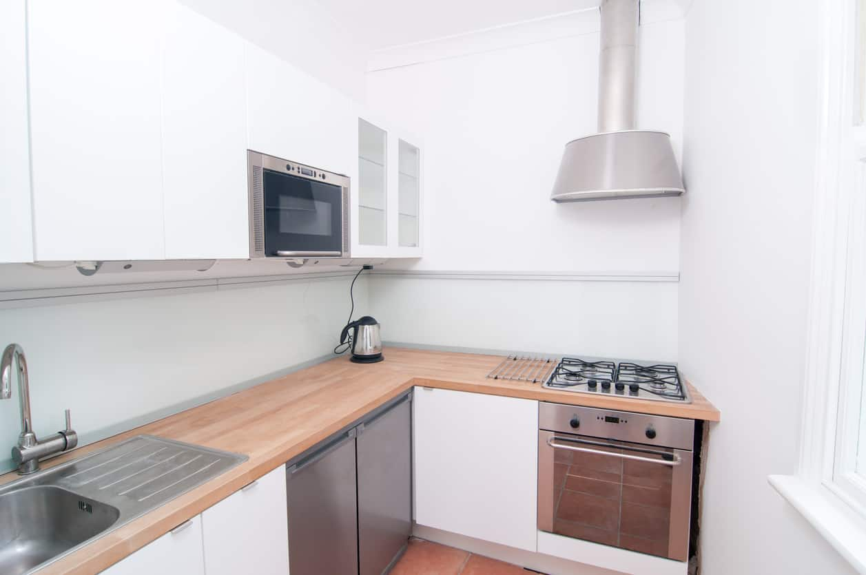 Cozy white kitchen in condo with wood countertops and stainless steel appliances. This has everything you need including a decent amount of counter space for such a small kitchen area.