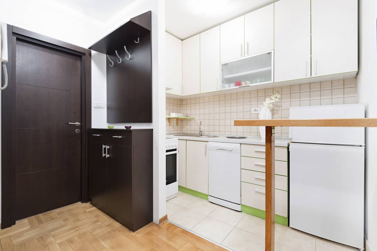 Tiny l-shaped white kitchen with green baseboards in an apartment. Small wood peninsula breakfast bar separates kitchen space from apartment entry.