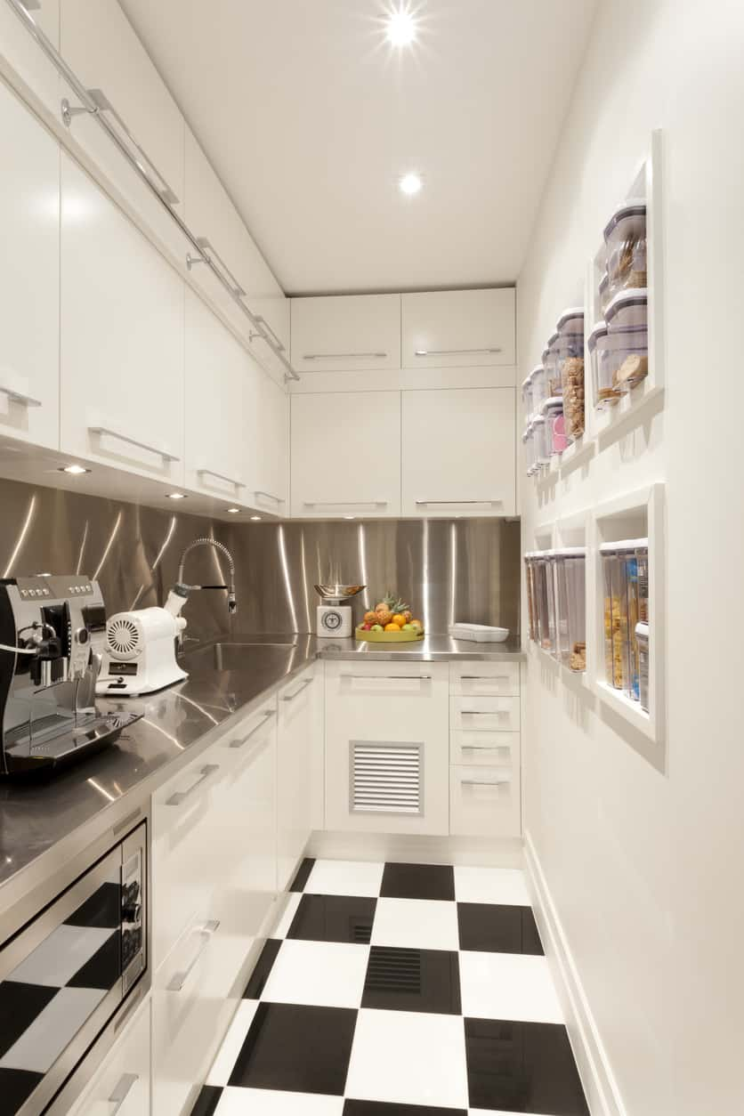 Fabulous tiny white kitchen with black and white checkered floor and check out the built-in mini pantry along the opposing wall... brilliant design. The interior designer