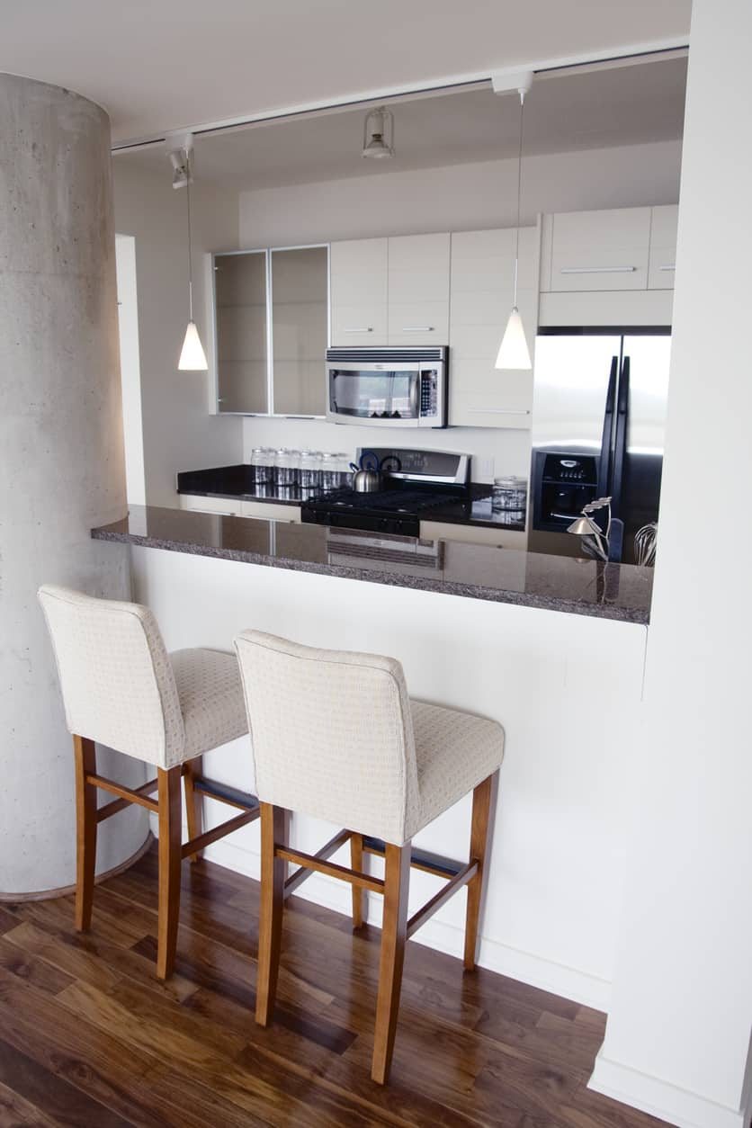 Tiny white kitchen with black countertops and breakfast bar peninsula that accommodates two kitchen bar stools.