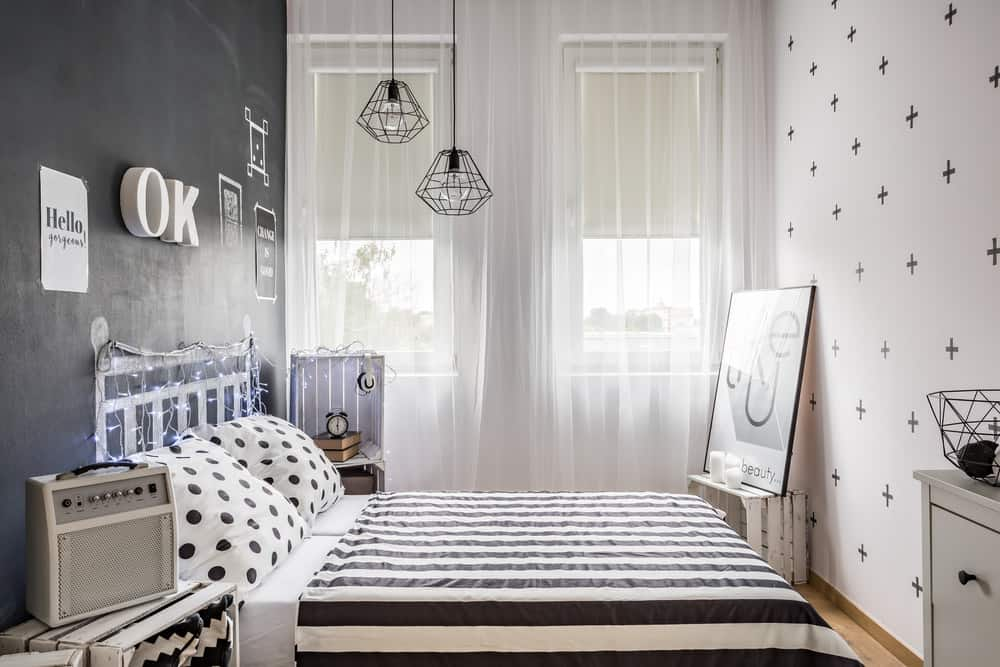 Fun tiny primary bedroom with quotes and interesting black and white decor throughout. It's interesting which mitigates the small size.