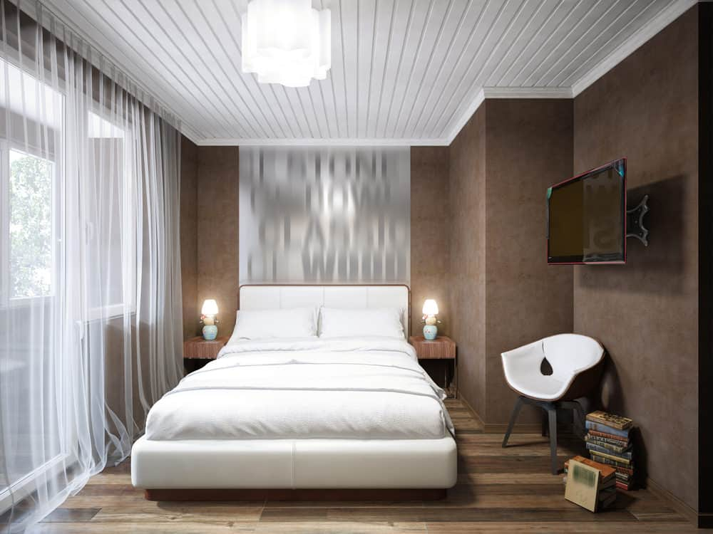 The designer for this primary bedroom uses dark and white contrast to create the illusion of a larger space. The white bed and white ceiling contrast nicely with the dark wood floor and walls.