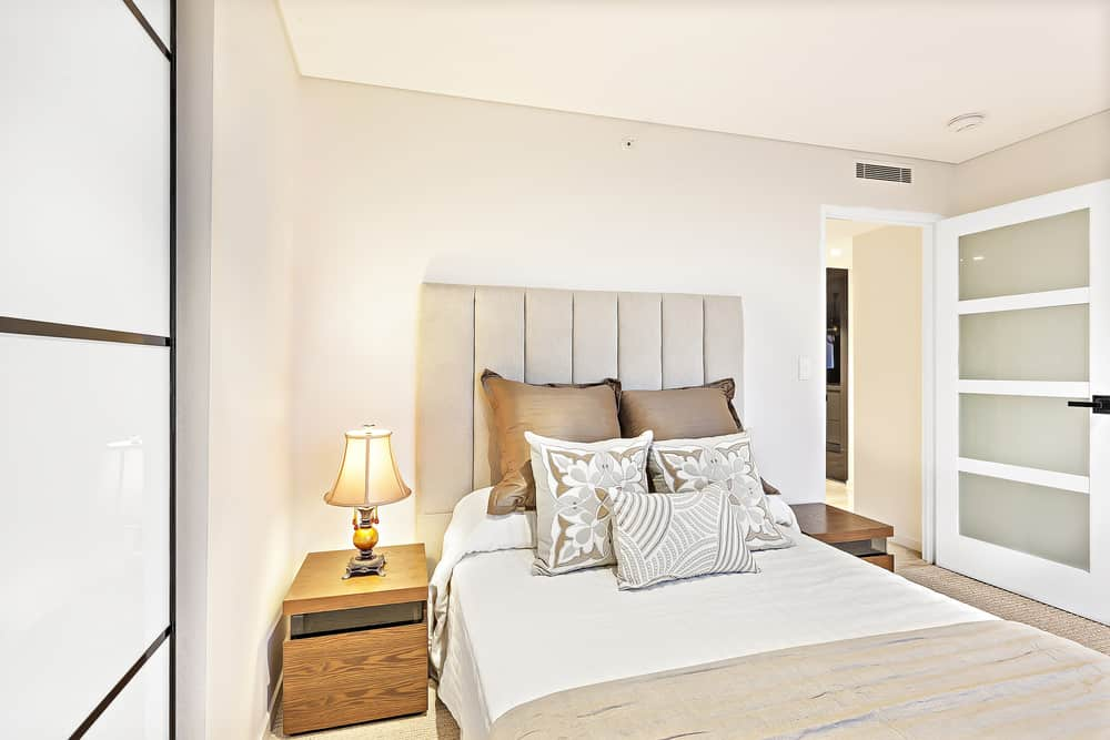 Here's a minimalist white primary bedroom in a small space.