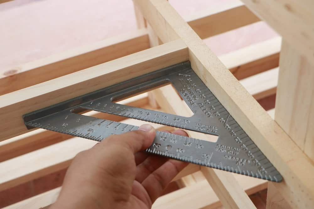 Hand holding a speed square at an angle on a wooden construction.