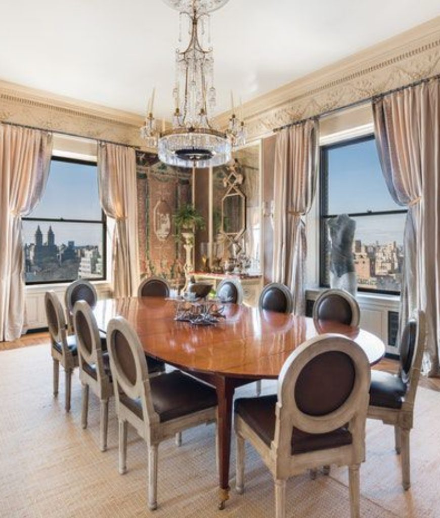 The dining room boasts an oval dining set with classy seats lighted by a chandelier.
