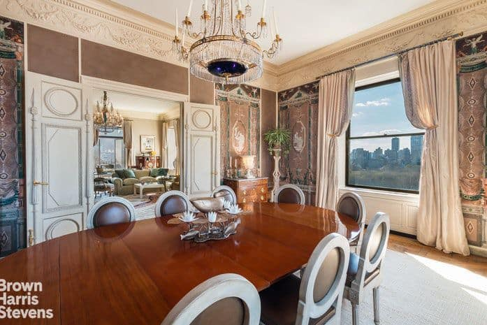 Another look at the dining room's table and chairs set along with a chandelier and stunning wall style.