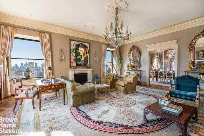 The living room boasts elegant furniture set along with a grand chandelier and a fireplace.