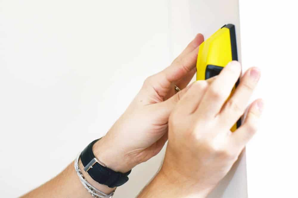 A pair of hands seen holding a yellow stud finder against a wall.