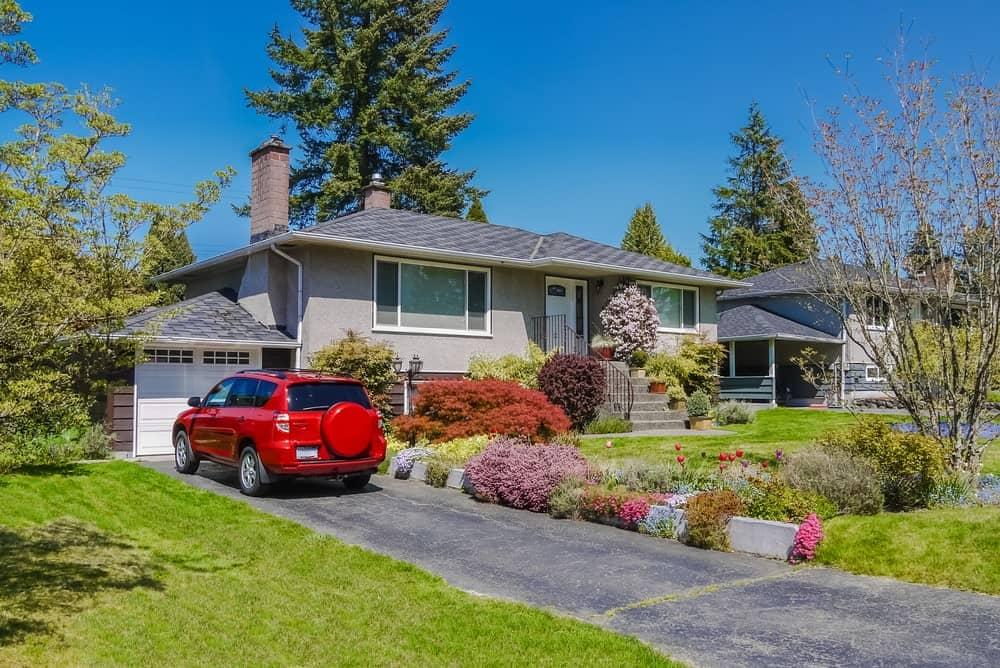 Suburban house with triplex unit, front garden, and asphalt driveway.
