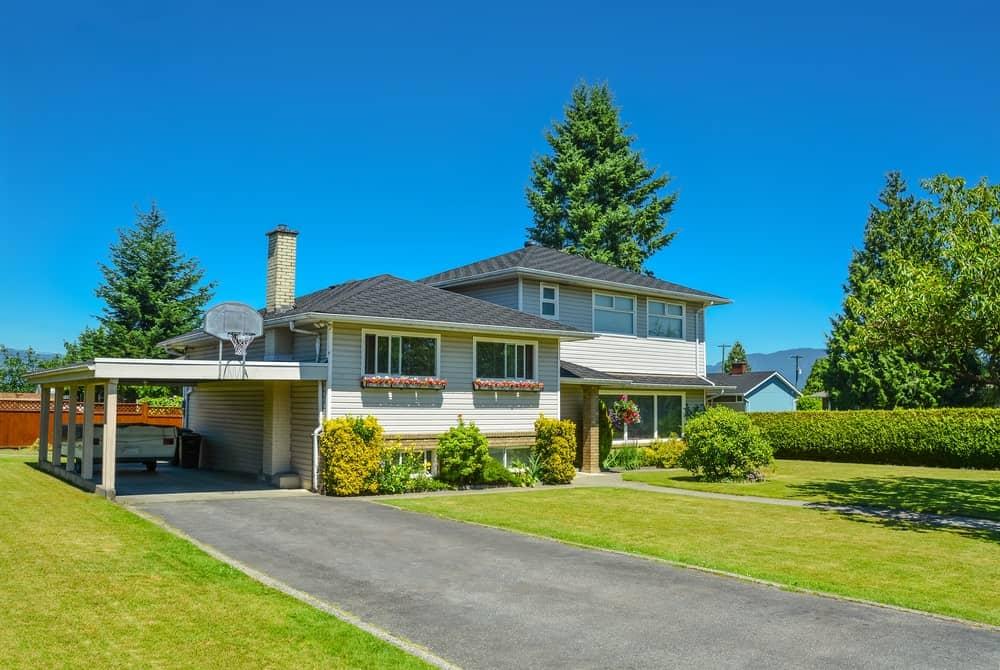 Suburban mansion with front lawn, duplex exterioir and asphalt driveway.