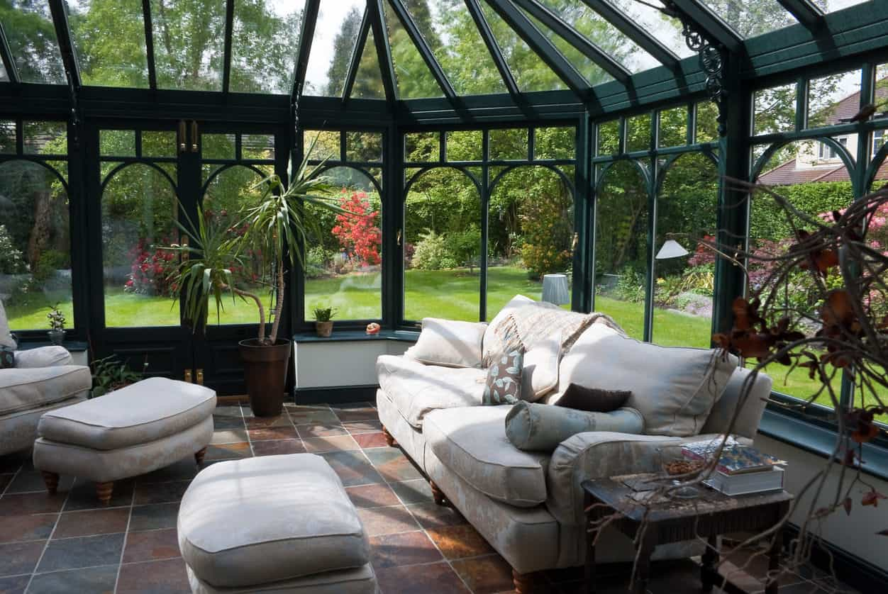 Large all-glass sunroom with sofa and other lounge furniture