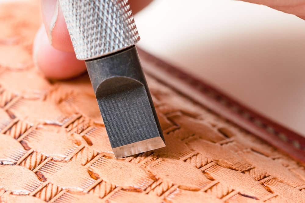 Using a swivel knife to carve out patterns on leather.