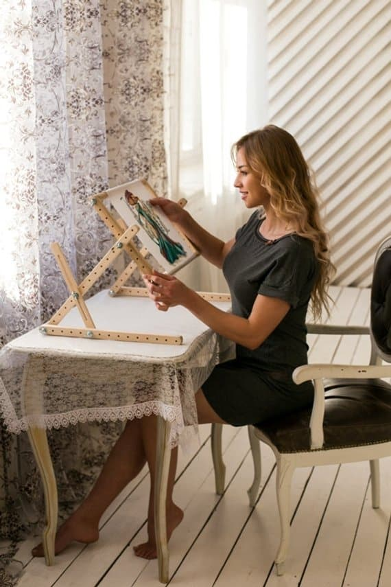 Woman doing an embroidery using a table stand.