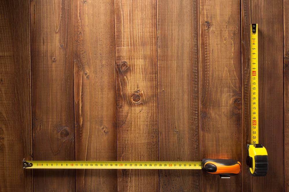 A pair of tape measures make an acute angle on wooden background.