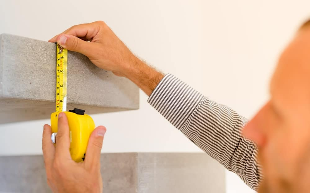 Man using tape measure to measure a cement block.