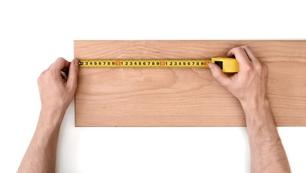 Person using a tape measure on a piece of wood.