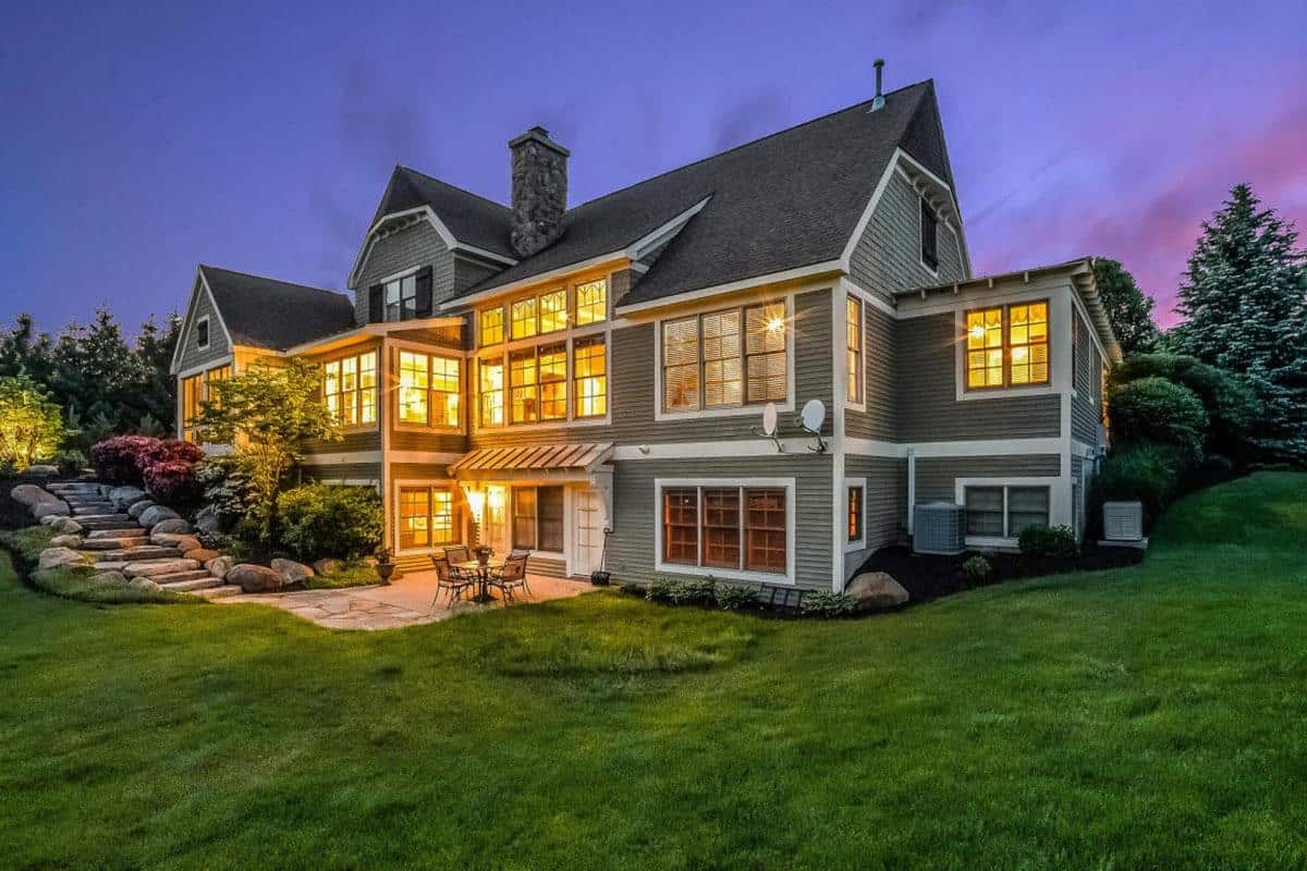 A gray farmhouse with a beautiful walkway and a breathtaking lawn and garden area.